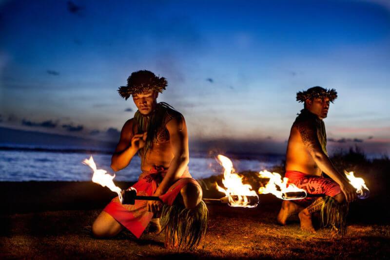 Two native Hawaiian men preparing for the fire dance performance.
